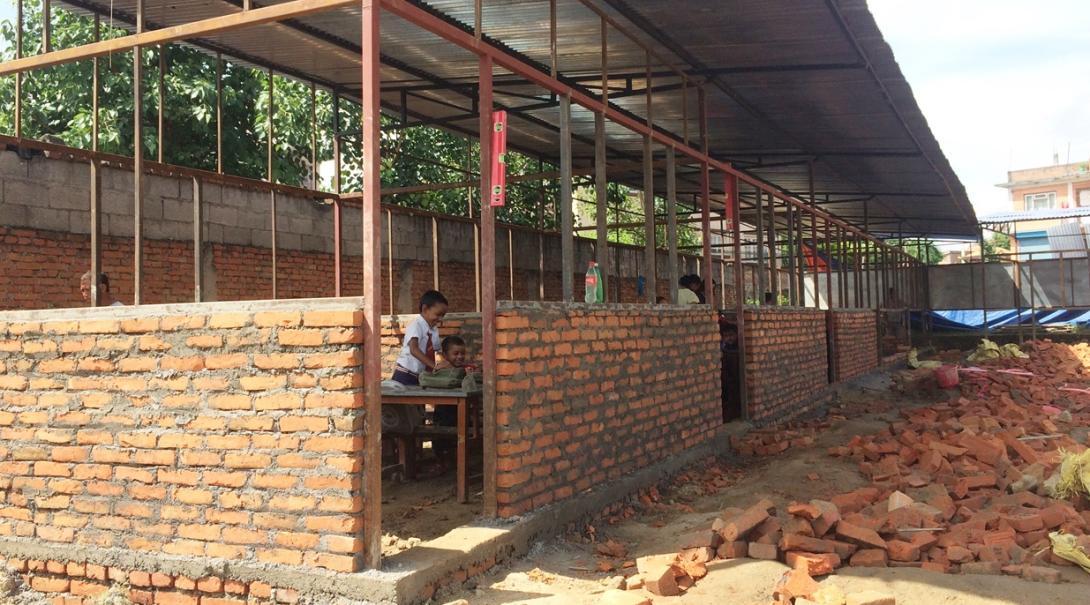 ネパールの再建された教室で学ぶ子供たち